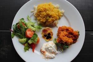 Vegetable curry, baked sweet potato, tahini, salad